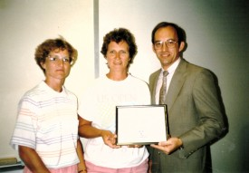 Sandy Hutchins, center, accepts an award from former SOILL President & CEo Doug Snyder and Amy Kaylor, left